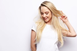 lifestyle and people concept - Beautiful happy blond girl touches her hair. Casual clothes. White background.