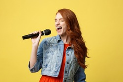 Lifestyle and People Concept: Expressive girl singing with a microphone, isolated bright yellow background.