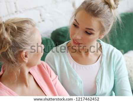 lifestyle  and people concept: Senior Woman With Adult Daughter Relaxing On Sofa At Home, close up #1217462452