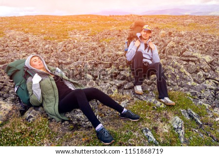 Lifestyle and survival concept rear view. Hiking women  and men with backpack  are very tired and lie on a halt, enjoying the trekking, in the background  mountains. Wanderlust and travel concept