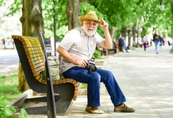 lifestyle and travel concept. man tourist use camera take photo. concept of photography. senior bearded man photographing outdoor. professional photographer designer. happy retirement. man on bench.