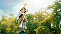 Lifestyle Asian family Father and son sat on his shoulders and run in  park. Paper plane as a toy in hand of kid And there are many big trees in garden Is natural in the morning of summer