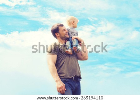 Lifestyle atmospheric photo happy father and son outdoors against blue sky with clouds - happy family, father\'s day and childhood concept