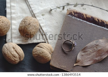 Lifestyle background with vintage book (carton cover texture looks like straus leather), nuts in shell, leaf, retro ring with gem. Healthy raw tasty vegan food. Education, read and eat. #1386493514