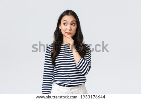 Lifestyle, beauty and fashion, people emotions concept. Thoughtful young asian girl searching for solution, thinking looking away and touching chin while pondering decision