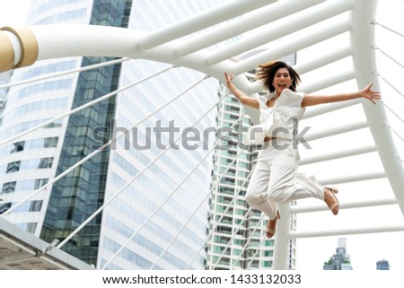 lifestyle business woman feel happy jumping in air celebrating  success and achievement on business district ,  business concept #1433132033