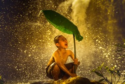 lifestyle children in Thai countryside. children playing water splash in the waterfall of natural.Children hold green umbrellas from nature in waterfall at countryside,Thailand.
