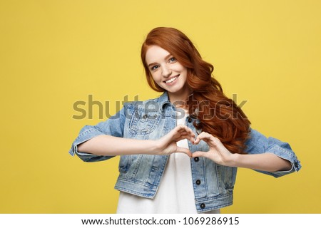 Lifestyle Concept: Beautiful attractive woman in denim making a heart symbol with her hands #1069286915