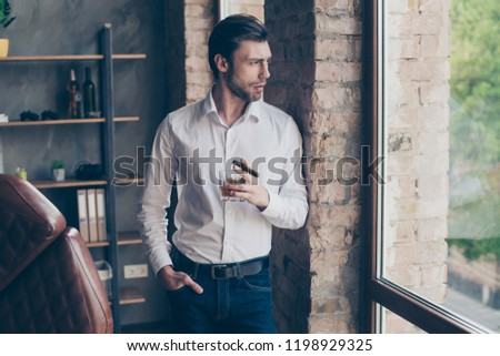 Lifestyle concept. Handsome brunet elegant attractive well-dressed good-looking in formal wear drink cognac liquor beverage liquid hold cigar in hand look aside on street stand in light indoor
