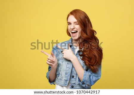 Lifestyle Concept: Happy excited cuacaisan tourist girl pointing finger on copy space isolated on golden yellow background