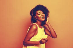 Lifestyle Concept - Portrait of beautiful African American woman joyful listening to music on mobile phone. pastel studio background. Copy Space