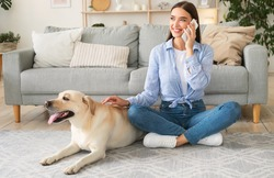 Lifestyle Concept. Portrait of casual smiling woman talking on smartphone, sitting together with cute golden retriever on the floor in living room. Female hipster rubbing her adorable domestic pet