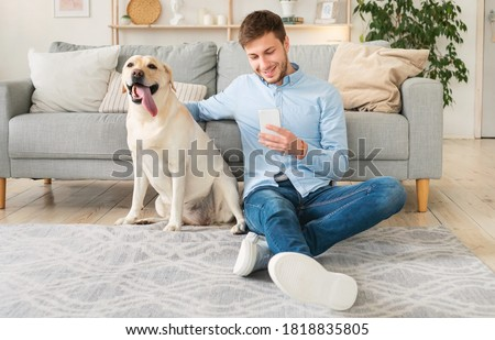 Lifestyle Concept. Portrait of smiling man using smartphone sitting on the carpet with his labrador, stroking dog. Guy spending time at home, chatting at social media, texting sms or reading message