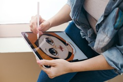 Lifestyle creative hobby and freelance artistic work job concept. Caucasian woman artist illustrator painting drawing on touch pad digital tablet with stylus. Process of creating illustration.
