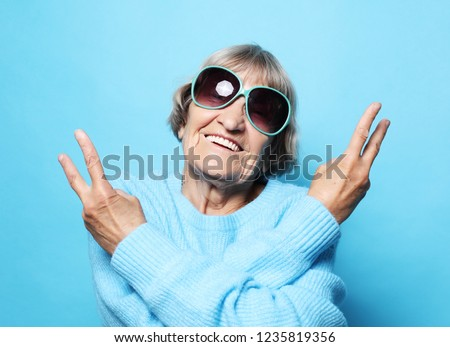 Lifestyle, emotion  and people concept: Funny old lady wearing blue sweater, hat and sunglasses showing victory sign. Isolated on blue background. #1235819356