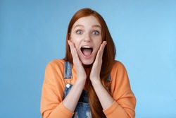 Lifestyle. Excited thrilled young emotional enthusiasitc ginger girl teenage college student yelling amused smiling broadly receive positive good news look surprised camera touch face astonished.