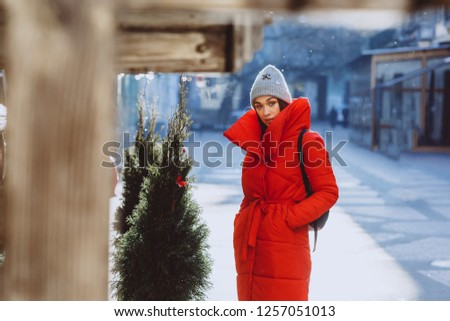 lifestyle fashion portrait of pretty young woman in red down jacket and grey knitted hat stay near christmas tree in new year street. Christmas, new year concept.