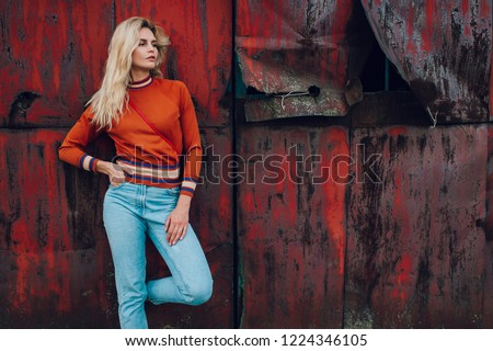 Lifestyle fashion portrait of young beautiful cute girl model.  Odd bizarre strange unusual cute naughty blonde babe posing on old rusty metal gate background. Nice looking woman in trendy clothes. #1224346105