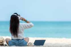 Lifestyle freelance woman listen music after using laptop working and relax on the beach.  Asia people success and together your work pastime and meeting conference on internet in holiday