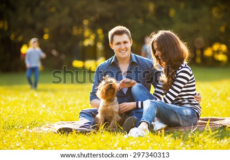 Lifestyle, happy family of two resting at a picnic in the park with a dog