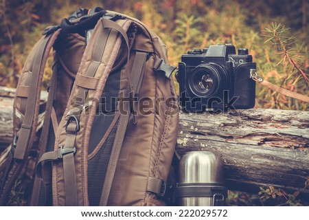 Lifestyle hiking camping equipment retro photo camera backpack and thermos outdoor forest nature on background