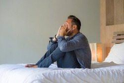 lifestyle home portrait of young attractive overwhelmed and depressed man sitting on bed worried and frustrated suffering depression crisis covering face with hands feeling desperate and helpless