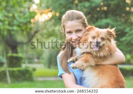 Lifestyle image of cute young woman holding dog and smiling. Loving dog in his owner\'s arms in the park. Concept of caring for a pet and animal adoption. Image with copy space for adding text or quote