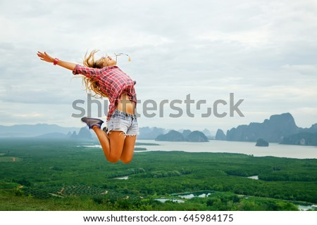 Lifestyle image of happy young traveling woman jumping carefree on nature background. In the mountains. Wearing stylish short shorts and checkered shirt. Freedom and happiness concept. In motion #645984175