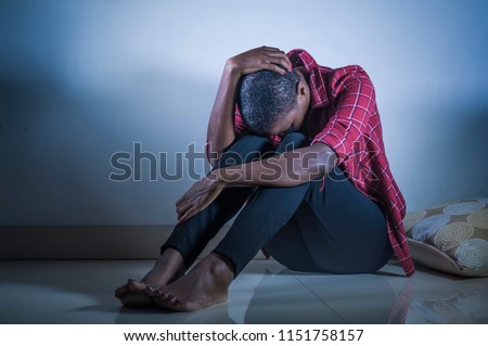 lifestyle indoors shady portrait of young sad and depressed black african American woman sitting at home floor feeling desperate and worried suffering pain and depression in dramatic light Photo stock ©