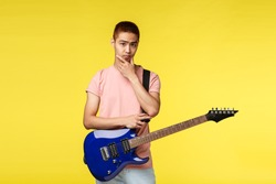 Lifestyle, leisure and youth concept. Unsure cute asian guy playing in band, thinking, making decision during band discussion what play, hold electric guitar, touch chin pondering at camera