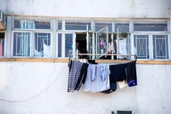 Lifestyle of Hong Kong people hanging dry clothes in the sun at outdoor of window of high building apartment at Kennedy Town in Hong Kong, China