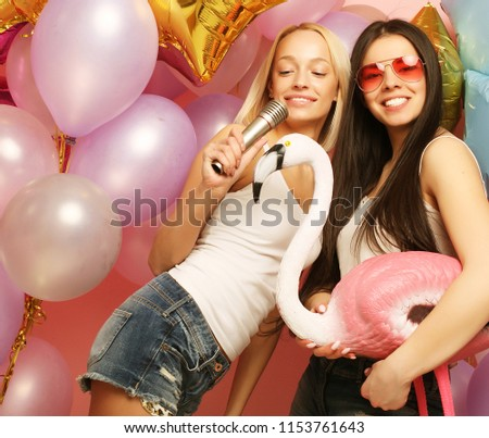 lifestyle, party  and people concept: Happy young girls with microphone and flamingo over вackground of  colorful balloons  #1153761643
