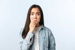 Lifestyle, people emotions and beauty concept. Anxious and concerned panicking asian girl grimacing, touching chin, look guilty or nervous, worried someone found out her fault