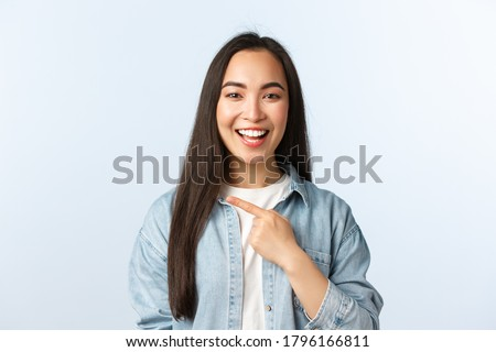 Lifestyle, people emotions and beauty concept. Happy laughing asian girl found something funny, showing way, pointing finger left, telling about big promo, special discounts at store