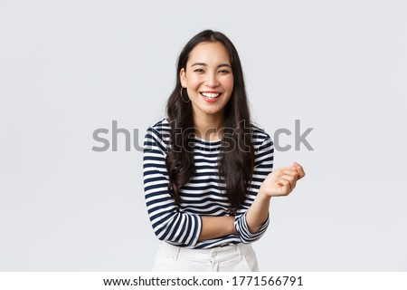Lifestyle, people emotions and casual concept. Carefree happy outgoing asian woman having fun talking to people, laughing and smiling upbeat, standing white background cheerful