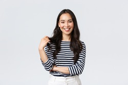 Lifestyle, people emotions and casual concept. Charming smiling korean girl in striped shirt, touching hair strand and grinning happily camera, talking to friend, white background