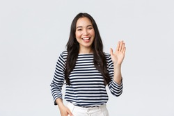 Lifestyle, people emotions and casual concept. Friendly cheerful asian woman smiling, saying hi and waving hand to greet person, make hello gesture, welcome someone