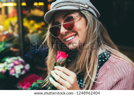 Lifestyle photo of beautiful young woman with pink rose. Bouquet as gift. Emotions of happiness and joy. Valentines day. Mothers day.Romantic girl with happy smile in vintage cap.Outdoors portrait.