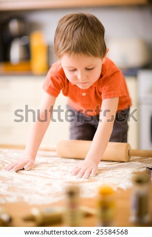 Lifestyle picture of little boy baking cookies.