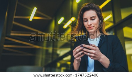 Lifestyle portrait business woman walking in evening city and using mobile gadget, girl banker dressed in business style listen to music wireless earphones and typing text message on smartphone device Stock photo ©