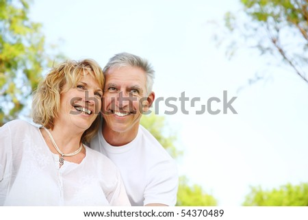 Lifestyle portrait of a mature couple smiling and embracing in the nature. Focus on the woman.