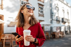 Lifestyle portrait of a young stylish woman in red shirt with coffee cup and smart phone walking on the street in the old city
