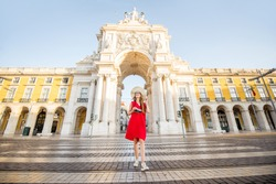 Lifestyle portrait of a young woman tourist walking in front of the famous triumphal arch in Lisbon city center in Portugal