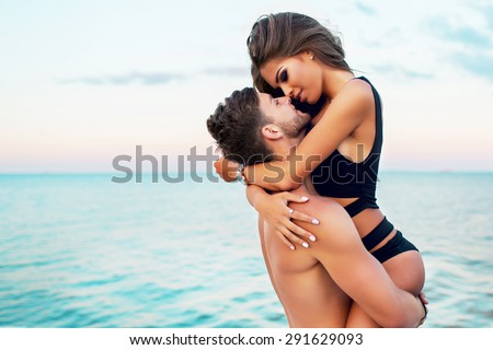 Lifestyle portrait of  attractive young woman and her handsome boyfriend keeps on  hands .  Beautiful couple  having fun sea background . Warm  evening colors.