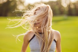 Lifestyle portrait of beautiful and happy  blonde woman with long hair in motion. Sunset outdoor, soft, warm sunny colors. Summertime and freedom concept.