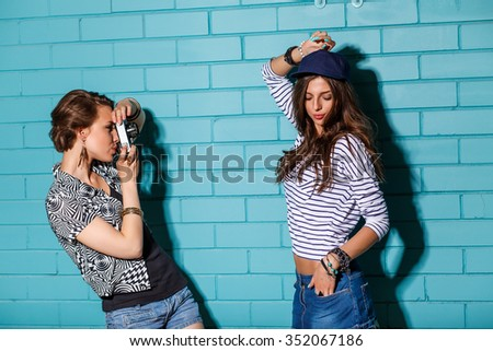 Lifestyle portrait of beautiful best friends hipster girls standing together near brick wall with photo camera and have fun while one taking picture of her friend dancing. Young active happy people.