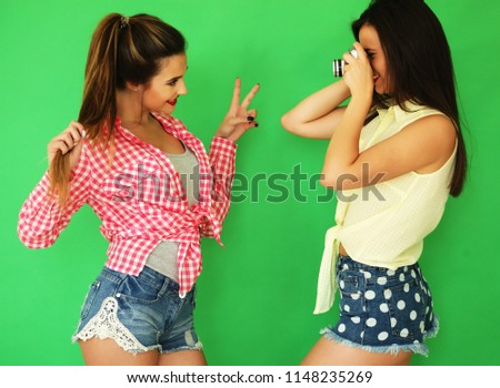 Lifestyle portrait of beautiful best friends hipster girls standing together with photo camera and have fun while one taking picture. Over green background.