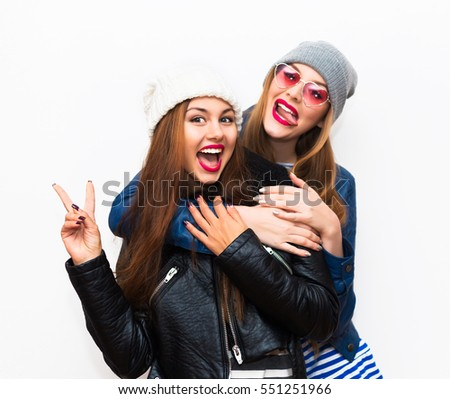 lifestyle portrait of two best friends hipster girls wearing stylish bright outfits, denim,leather coat and glasses, going crazy and having great time together.Laughing and send kiss,lovely girls #551251966