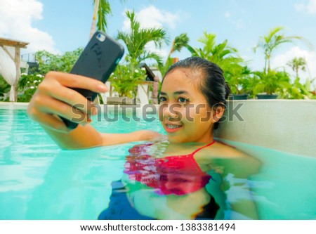 lifestyle portrait of young happy and beautiful Asian Indonesian teen girl in bikini taking selfie picture with mobile phone in beach hotel swimming pool relaxed at tropical resort having fun