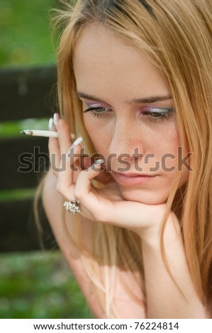 Lifestyle portrait of young worried and depressed woman smoking cigarette outdoors